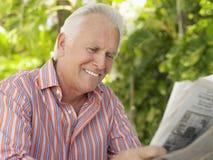 Усмехаясь зрелая газета чтения человека стоковая фотография
