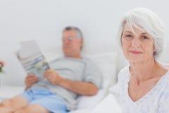 Усмехаясь зрелая женщина сидя в кровати Стоковая Фотография
