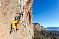 Усмехаясь зрелая мужская весьма смертная казнь через повешение альпиниста на скалистой стене легкой стоковое изображение