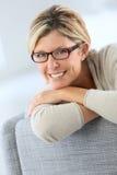 Усмехаясь зрелая склонность женщины на софе Стоковые Фото