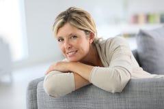 Усмехаясь зрелая склонность женщины на софе Стоковые Изображения
