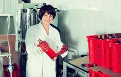 Усмехаясь зрелые бутылки вина женского работника упаковывая Стоковые Изображения