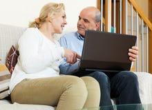 Усмехаясь зрелые пары с компьтер-книжкой Стоковая Фотография RF