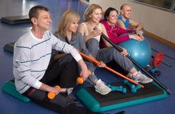 Усмехаясь зрелые человек и женщина представляя в спортзале Стоковые Фото
