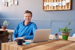 Усмехаясь зрелый бизнесмен работая на компьтер-книжке в офисе Стоковая Фотография