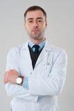 Усмехаясь зрелый мужской доктор с пересеченными оружиями изолированный на сером ба Стоковые Фото