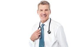 Усмехаясь зрелый доктор изолированный на белизне стоковые фото