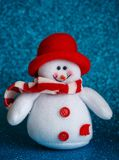 Усмехаясь игрушка снеговика одела в шарфе и крышке на абстрактной предпосылке bokeh Стоковые Фотографии RF