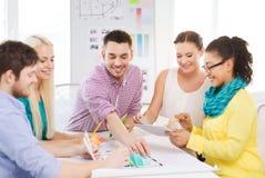 Усмехаясь дизайнеры по интерьеру работая в офисе стоковые изображения