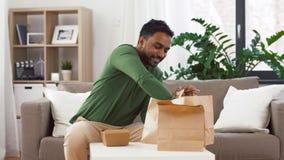 Усмехаясь индийский человек распаковывая на вынос еду дома видеоматериал