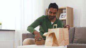 Усмехаясь индийский человек распаковывая на вынос еду дома акции видеоматериалы