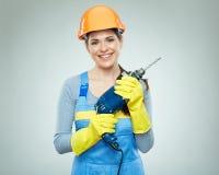 Усмехаясь инструмент сверла удерживания шлема женщины нося Стоковые Фотографии RF