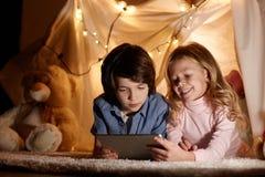 Усмехаясь интернет мальчика и девушки занимаясь серфингом на доске сзажимом для бумаги Стоковое Фото