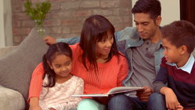 Усмехаясь испанская семья в живущей комнате сток-видео