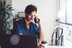 Усмехаясь испанский бизнесмен работая современный мобильный компьютер пока сидящ на деревянном столе на солнечном офисе человек Стоковая Фотография