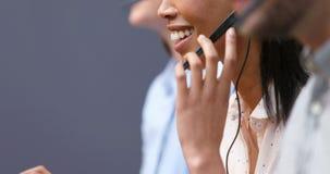 Усмехаясь исполнительные власти обслуживания клиента говоря на шлемофоне на столе 4k акции видеоматериалы