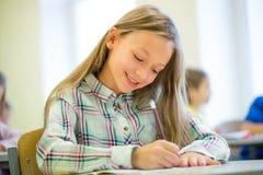 Усмехаясь испытание сочинительства девушки школы в классе Стоковое фото RF