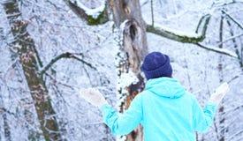 Усмехаясь кавказская девушка в сером цвете связала mittens и шляпу Лес Snowy на заднем плане Зима Снег вокруг стоковое изображение rf