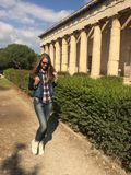 Усмехаясь кавказская девушка в солнечных очках Девушка с длинными волосами в костюме джинсовой ткани и белых тапках девушка идя в Стоковая Фотография RF