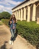 Усмехаясь кавказская девушка в солнечных очках Девушка с длинными волосами в костюме джинсовой ткани и белых тапках девушка идя в Стоковые Изображения