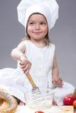Усмехаясь кавказская девушка в форме кашевара делая смешивание из муки, яичка и овощи с юркнут Стоковое Изображение RF