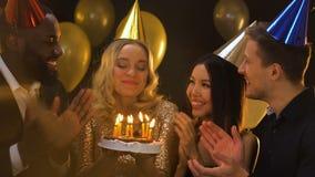 Усмехаясь кавказская женщина в свечах на торте, торжестве b-дневной шляпы дуя видеоматериал