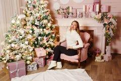 Усмехаясь кавказская женщина сидя в стуле около рождественской елки стоковое изображение rf