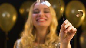 Усмехаясь кавказская женщина со светом Бенгалии под падая confetti, партией Нового Года сток-видео