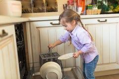 Усмехаясь кавказская порция девушки в кухне принимая плиты из Стоковая Фотография