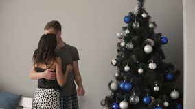 Усмехаясь кавказские молодые пары украшая ель с причудливыми голубыми и серебряными покрашенными шариками Молодая семья совместно сток-видео