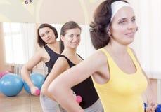 3 усмехаясь кавказских женщины имея тренировку разминки с штангами внутри помещения Стоковое Изображение