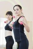 2 усмехаясь кавказских женщины спорт работая с штангами Стоковое Изображение