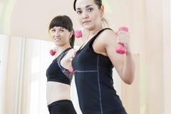 2 усмехаясь кавказских женщины спорт работая с штангами Стоковые Фото