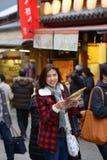 Усмехаясь карта владением женщины туристская стоковые фотографии rf