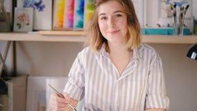 Усмехаясь картина художника довольная белокурая женская сток-видео