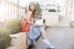 Усмехаясь кассета усаживания и чтения молодой женщины в городе Стоковая Фотография