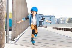 Усмехаясь катание на ролике мальчика практикуя на катке Стоковые Изображения RF