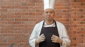 Усмехаясь кашевар стоя в kitchennd говоря к камере о блюде он идет подготовить Стоковое Изображение RF
