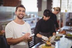 Усмехаясь кельнер стоя против женских шеф-поваров подготавливая еду в кухне Стоковая Фотография RF