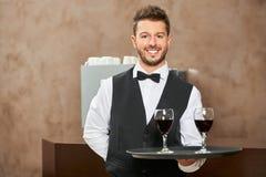 Усмехаясь кельнер служа красное вино в ресторане Стоковая Фотография RF