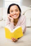 Усмехаясь книга чтения брюнет Стоковое Фото