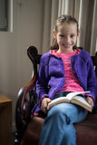 Усмехаясь книга чтения девушки на стуле в живущей комнате Стоковые Фотографии RF