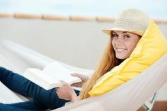Усмехаясь книга чтения женщины в гамаке Стоковая Фотография RF