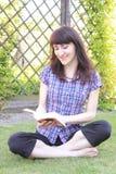 Усмехаясь книга чтения женщины на траве в саде Стоковое Фото