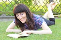 Усмехаясь книга чтения женщины на траве в саде Стоковое Изображение