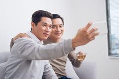 2 усмехаясь коллеги принимая изображению к им усаживание i собственной личности Стоковая Фотография