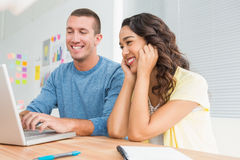 Усмехаясь коллеги работая вместе с компьтер-книжкой Стоковая Фотография RF