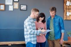 3 усмехаясь коллеги работы обсуждая обработку документов совместно в офисе Стоковые Изображения RF