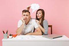 2 усмехаясь коллеги человека бизнес-леди сидят работа на белом столе с современным изолированным ноутбуком на пастельной розовой  стоковое изображение