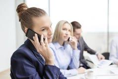 Усмехаясь команда дела с smartphones в офисе Стоковая Фотография
